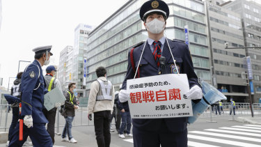 A security guard urges people not to watch a half-marathon in Sapporo in northern Japan on Wednesday to curb the spread of COVID-19.