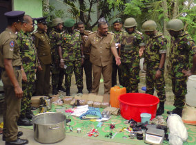 Sri Lankan police and army officers display bomb making materials recovered from a hideout of militants after Friday's gun battle.