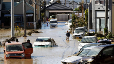 Vehicles are seen in mud water as Typhoon Hagibis hit the city in Sano, Tochigi prefecture.