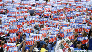 Protesters display signs against a planned US military base relocation during a rally in Naha, Okinawa prefecture, on the southern Japanese island on Saturday.