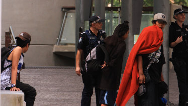 Police move a group of homeless young people on from King George Square in Brisbane.