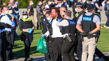 A man is taken away by police at the Shrine of Remembrance.