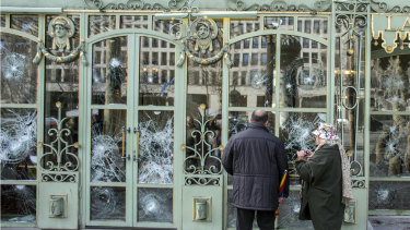 Bystanders take snapshots of the smashed windows of the famed tea salon Laduree on the Champs Elysees the day after it was vandalised during the 18th straight weekend of demonstrations by the yellow vests in Paris.