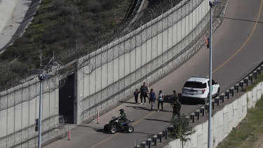 Honduran asylum seekers are taken into custody by US Border Patrol agents after the group crossed the US border wall into San Diego, California.