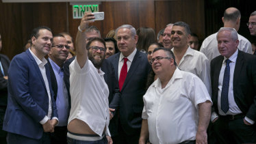Knesset member Oren Hazan takes a selfie with Israel's Prime Minister Benjamin Netanyahu, centre, and MP David Bitan, right of Netanyahu, after a Knesset session that passed a contentious bill, in Jerusalem on Thursday.