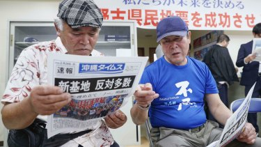 People take a look at a copy of a local newspaper reporting a referendum in Naha, Okinawa, Japan, on Sunday.