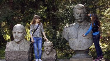 Girls joke around with statues of Soviet founder Vladimir Lenin, left, Felix Dzerzhinsky, centre, founder of the first Soviet secret police force and Soviet ruler Josef Stalin, right, at the Grutas Park in Druskininkai, Lithuania.