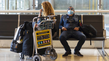 Passengers wear protective face masks at Madrid Barajas airport. Spain's death toll from the coronavirus has passed 1,000.