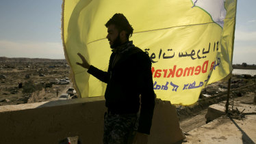 A US-backed Syrian Democratic Forces (SDF) fighter stands on a rooftop overlooking Baghouz, Syria, after the SDF declared the area free of Islamic State militants last month.