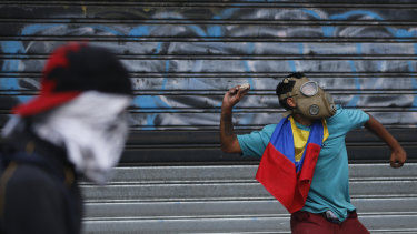 An anti-government protester winds up to throw a rock at security forces during clashes in Caracas.