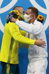 Kyle Chalmers and Caeleb Dressel embrace after the medal ceremony.