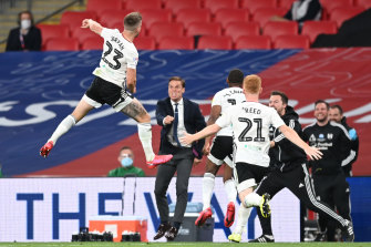 A leaping Joe Bryan celebrates scoring Fulham's first goal against Brentford at Wembley.