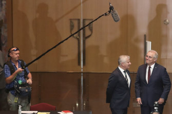 Michael McCormack in discussion with Scott Morrison as he spots a microphone above them.
