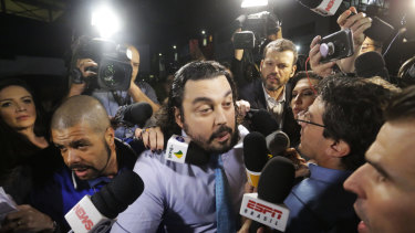 Danilo Garcia de Andrade, centre, lawyer for Najila Trindade, speaks with reporters as he arrives to a police station in Sao Paulo, Brazil, on Thursday.