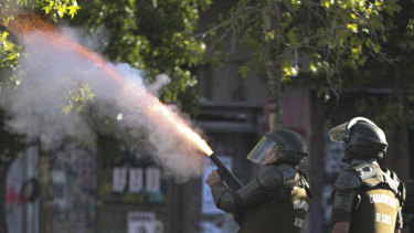 A police officer fires a tear gas canister at anti-government demonstrators during a protests in Santiago, Chile.