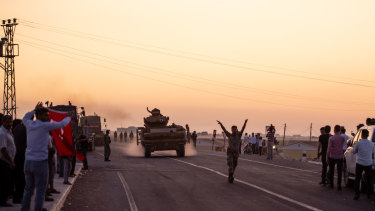 People wave as Turkish soldiers prepare to cross the border into Syria.