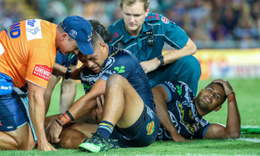 Play on: Cowboys duo John Asiata (left) and Nene Macdonald are attended to after their brutal collision last Friday night.