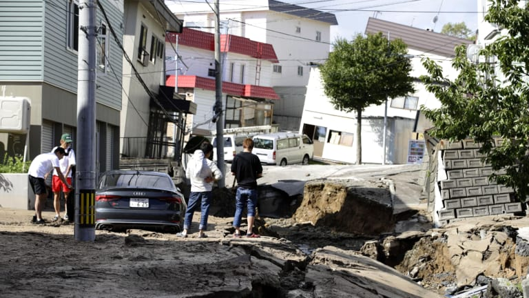 Houses stand at an angle and a road has been ripped up in Sapporo.