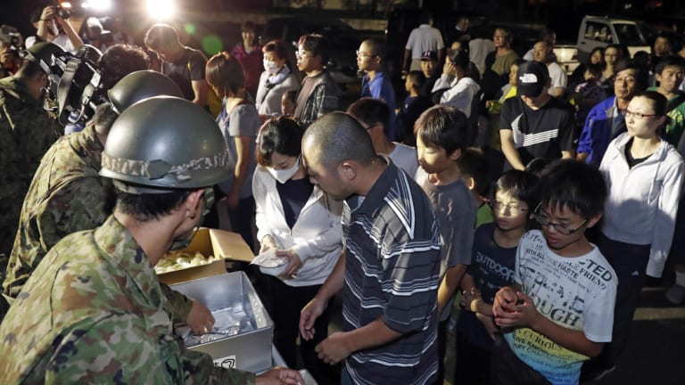 People wait to receive food at a shelter in Atsuma, Hokkaido, on Thursday night.