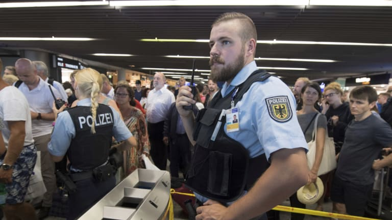 Police guard the hall of Terminal 1 after a family that tested positive for explosives were allowed to leave a secure area.