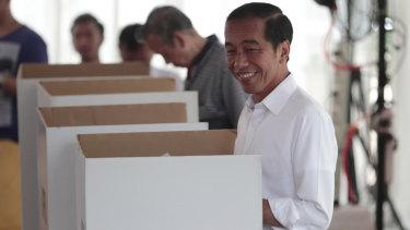 "Indonesian President Joko ""Jokowi"" Widodo smiles as he votes in Jakarta on Wednesday."