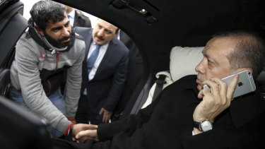 Recep Tayyip Erdogan holds a citizen by the hand while speaking on his iPhone in 2015. He is now calling for a boycott of American products, including the iPhone.