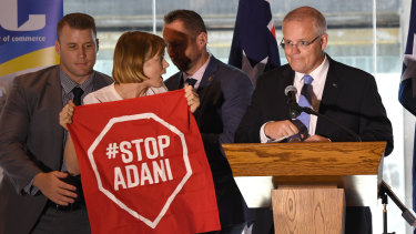 Not about to depart centre stage: An anti-Adani protester about to be led away after interrupting Prime Minister Scott Morrison's speech in Brisbane on Monday.