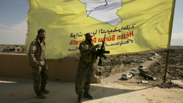 U.S.-backed Syrian Democratic Forces (SDF) fighters pose for a photo on a rooftop overlooking Baghouz, Syria, after the SDF declared the area free of Islamic State militants after months of fighting on Saturday, March 23, 2019. The elimination of the last Islamic State stronghold in Baghouz brings to a close a grueling final battle that stretched across several weeks and saw thousands of people flee the territory and surrender in desperation, and hundreds killed.  (AP Photo/Maya Alleruzzo)