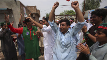 Supporters of politician Imran Khan dance to celebrate the victory of their party candidate, in Peshawar, Pakistan.