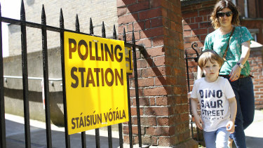 A woman and child leave a polling station after casting her vote in the referendum on the 8th Amendment of the Irish Constitution, in Knock.