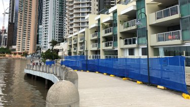 Repairs are needed along a stretch of the Brisbane City Council-managed riverwalk under large planter boxes between the riverwalk and an apartment building behind it.