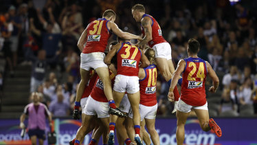 Brisbane Lions players celebrate an after the siren goal to win the game by Zac Bailey.