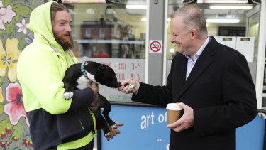 Opposition Leader Anthony Albanese meets Yass local Daniel Halloran and shakes paws with his dog Ripley.