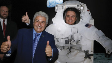 Brazilian Minister of Science and Technology Marcos Cesar Pontes, left, with President Jair Bolsonaro, standing behind a cardboard cutout of a US astronaut, at the US Embassy celebrating the 50th anniversary of the Apollo 11 moonwalk, in Brasilia, Brazil.