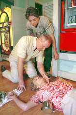 Alf Stewart (Meagher) and his son Duncan (Brendan McKensy) rushing to the aid of Ailsa Stewart (Judy Nunn) after she suffers from a heart attack.