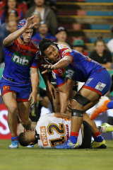 Kalyn Ponga, left, motions to the sideline after his hit on Michael Chee Kam.