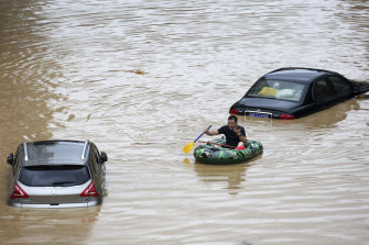 A man paddles past submerged cars during a flood in Rongshui County in southern China's Guangxi Zhuang Autonomous Region.