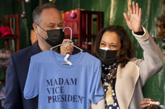 "Vice President-elect Kamala Harris, accompanied by her husband Doug Emhoff, left, holds up a T-shirt as they visit the ""made in DC"" booth in the Downtown Holiday Market in Washington."