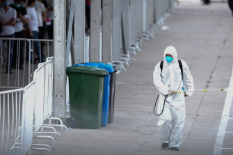 A worker disinfects a site where Beijing residents are being tested for COVID-19.