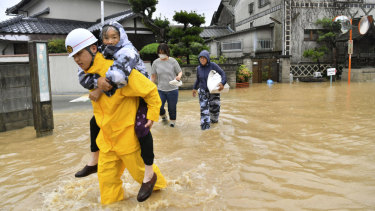 Residents are evacuated to a safer place from floodwaters in Kurashiki, Okayama prefecture, Japan.