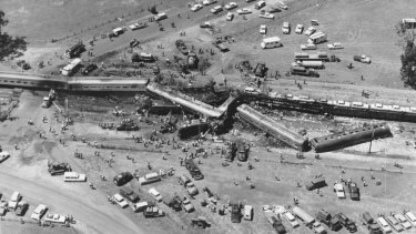 An aerial view of the crash scene with the Southern Aurora and freight train surrounded by rescue vehicles.