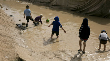 Children play in a mud puddle in the section for foreign families at Al-Hol camp in Hasakeh province, Syria.