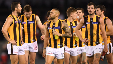 Dejected Hawks leave the field after losing to Essendon.