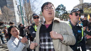 Police remove a supporter of Beijing on Saturday morning during the second rally in two days in Melbourne in support of Hong Kong democracy protesters.