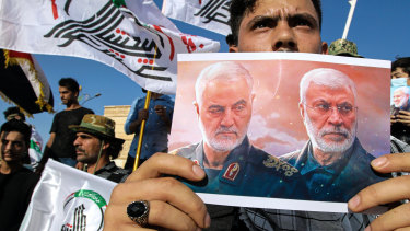 A supporter of an Iran-backed militia holds a poster of slain Iranian General Qassem Soleimani, left, and deputy commander Abu Mahdi al-Muhandis during a protest by pro-Iranian militiamen in Iraq last year.