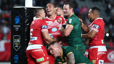 Red and white parade: Tonga celebrate Will Hopoate's try.
