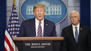 Donald Trump speaks as Vice-President Mike Pence looks on. The White House is moving against the WHO on several fronts.