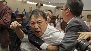 Pro-democracy lawmaker Wu Chi-wai, centre, is restrained by security guards at the Legislative Council in Hong Kong, on Saturday.