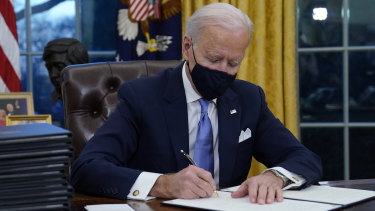 President Joe Biden signs his first executive orders in the Oval Office of the White House.
