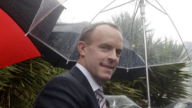 Britain's Foreign Secretary Dominic Raab shelters from the rain in Sydney, in February, at a visit to the British-Swedish multinational biopharmaceutical company, AstraZeneca.